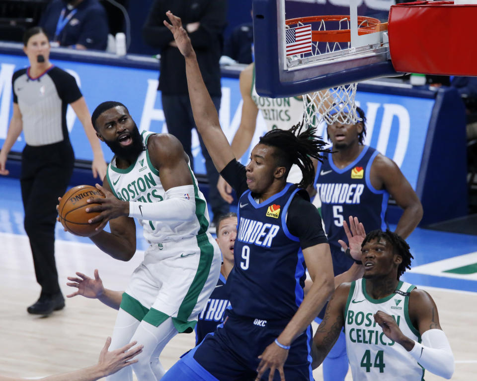 Boston Celtics guard Jaylen Brown (7) goes against Oklahoma City Thunder center Moses Brown (9) as Thunder center Isaiah Roby and forward Luguentz Dort (5) and Celtics center Robert Williams III (44) watch during the first half of an NBA basketball game Saturday, March 27, 2021, in Oklahoma City. (AP Photo/Garett Fisbeck)
