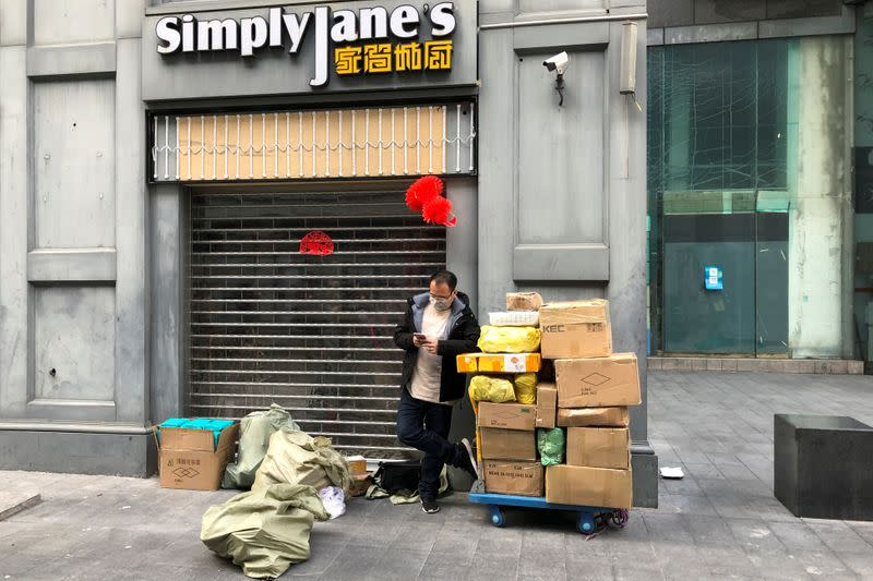 Man wearing a face mask checks his mobile phone next to a trolley of boxes on the streets of Huaqiangbei following an outbreak of the novel coronavirus in the country`