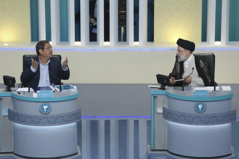 """In this picture made available by Young Journalists Club, YJC, presidential candidate for June 18, elections Abdolnasser Hemmati, left, speaks as Ebrahim Raisi listens in the final debate of the candidates, at a state-run TV studio in Tehran, Iran, Saturday, June 12, 2021. Iran's seven presidential candidates offered starkly different views Saturday in the country's final debate, with hard-liners describing those seeking ties with the West as """"infiltrators"""" and the race's sole moderate warning a hard-line government would only bring more sanctions for the Islamic Republic. (Morteza Fakhri Nezhad/ Young Journalists Club, YJC via AP)"""