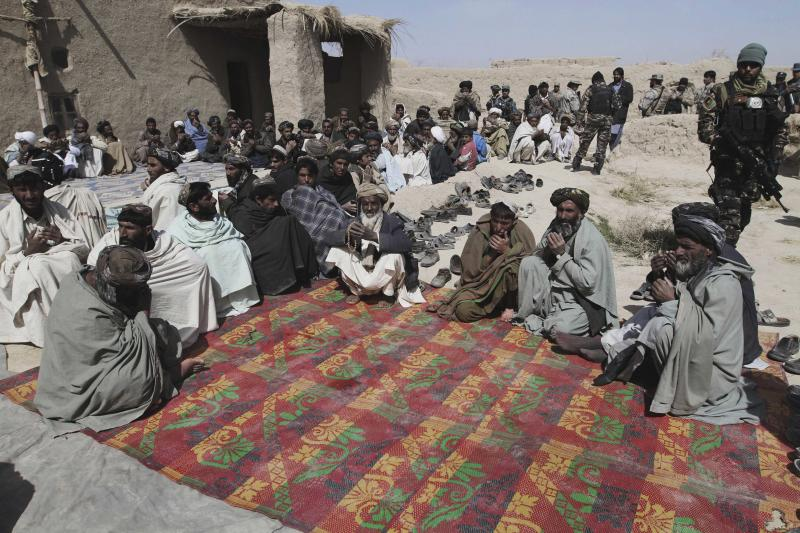 Afghan villagers pray during a prayer ceremony for the victims of Sunday's killing of civilians by a U.S. soldier in Panjwai, Kandahar province south of Kabul, Afghanistan, Tuesday, March. 13, 2012. Taliban militants opened fire Tuesday on a delegation of senior Afghan officials including two of President Hamid Karzai's brothers visiting villages in southern Afghanistan where a U.S. soldier is suspected of killing 16 civilians. (AP Photo/Allauddin Khan)