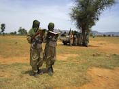 In this Thursday, Sept. 27, 2012 photo, two young fighters read out Quranic verses for a journalist, at the request of their Islamist commanders, in Douentza, Mali. Across northern Mali, Islamists have plucked and paid for as many as 1,000 children from rural towns and villages devastated by poverty and hunger, The Associated Press has found. Interviews conducted by the AP provide evidence that a new generation in what was long a moderate and stable Muslim nation is becoming radicalized, as the Islamists gather forces to fight a potential military intervention backed by the United Nations. (AP Photo/Baba Ahmed)
