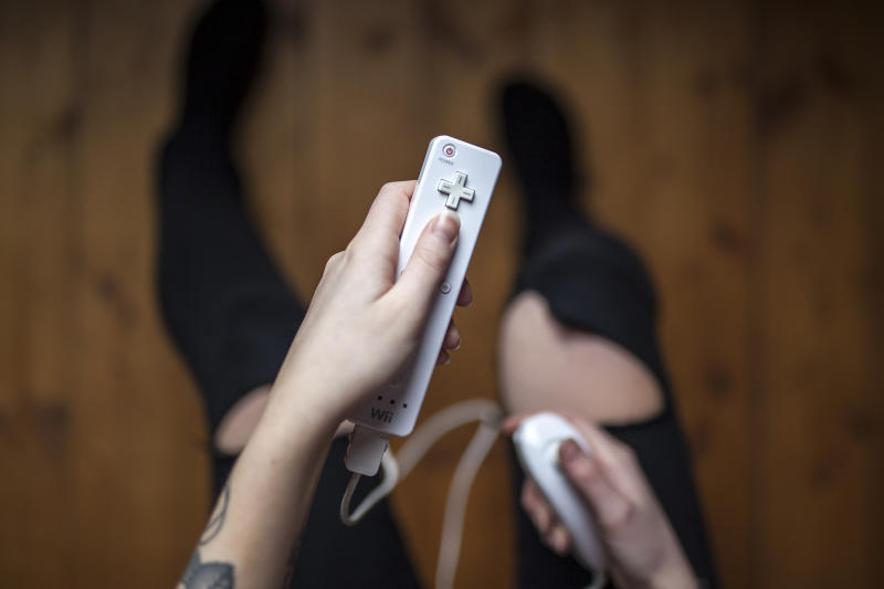 Gothenburg, Sweden - January 17, 2015: A shot from above of a young woman's hands holding Wii remote with Nunchuck, a game pad controller for the Nintendo Wii video game console developed by Nintendo Co., Ltd. Natural lighting. Shot on wooden background.