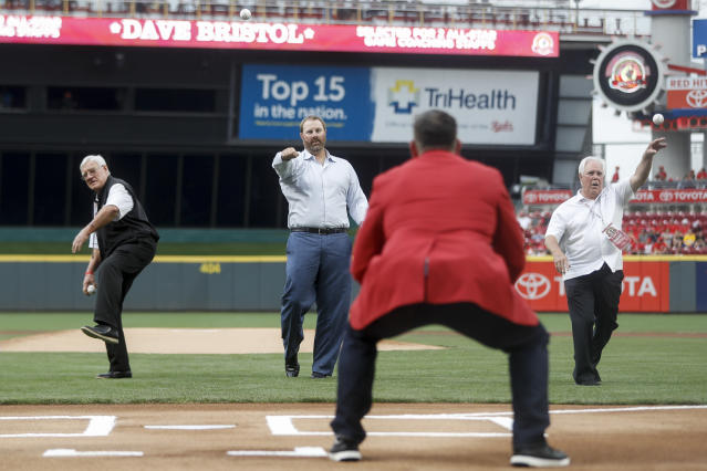 Cincinnati Reds Hall of Fame inductees, from back left to right, Dave Bristol, Adam Dunn and Fred Norman, throw out ceremonial first pitches during their induction ceremony before a baseball game against the Pittsburgh Pirates, Saturday, July 21, 2018, in Cincinnati. (AP Photo/John Minchillo)