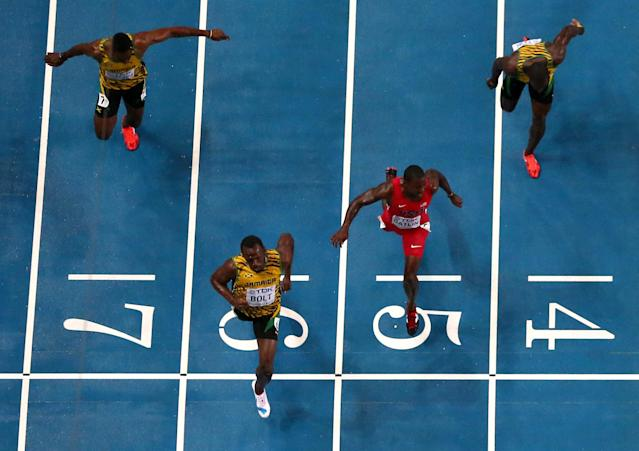MOSCOW, RUSSIA - AUGUST 11: Usain Bolt of Jamaica (C) crosses the line to win gold ahead of Kemar Bailey-Cole of Jamaica, Justin Gatlin of the United States and Nickel Ashmeade of Jamaica in the Men's 100 metres Final during Day Two of the 14th IAAF World Athletics Championships Moscow 2013 at Luzhniki Stadium on August 11, 2013 in Moscow, Russia. (Photo by Julian Finney/Getty Images)