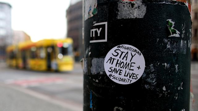 A sticker on a pole in Germany implores people to stay home amid the battle against the coronavirus pandemic. (Photo by Ronny Hartmann / AFP) (Photo by RONNY HARTMANN/AFP via Getty Images)