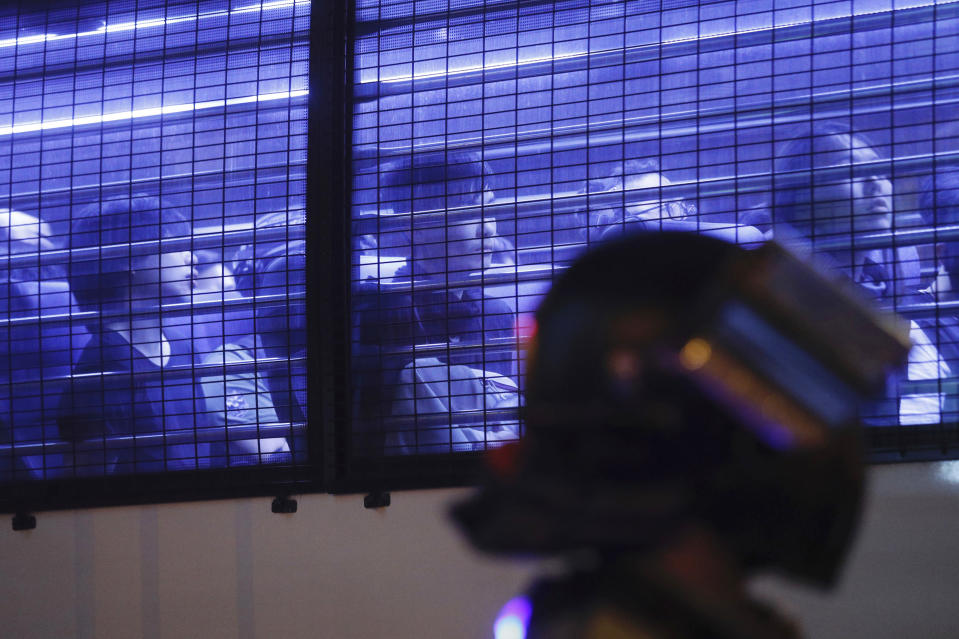 Detained protesters are seen in a police vehicle in Hong Kong on Sunday, Oct. 27, 2019. Hong Kongers rallied Sunday over concerns about police conduct in months long pro-democracy demonstrations, including exposing police dogs to tear gas during chaotic confrontations with protesters. (AP Photo/Kin Cheung)