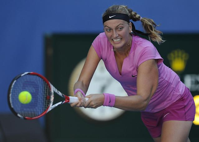 Petra Kvitova of the Czech Republic makes a backhand return to Luksika Kumkhum of Thailand during their first round match at the Australian Open tennis championship in Melbourne, Australia, Monday, Jan. 13, 2014. (AP Photo/Andrew Brownbill)