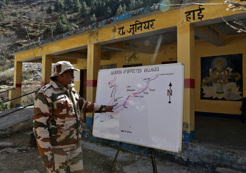 An Indo-Tibetan Border Police (ITBP) officer explains the location of affected villages on a map at a temporary base camp set up by ITBP for distribution of relief material in the affected areas, at Lata village