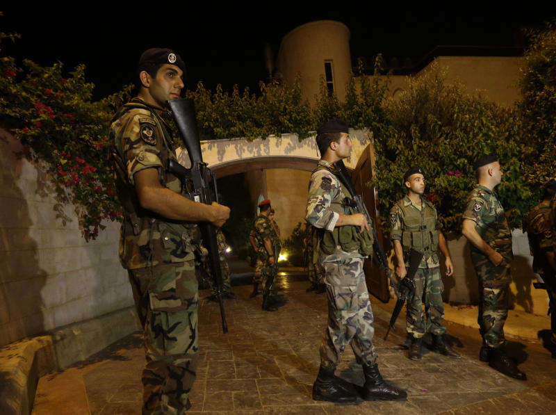 Lebanese army soldiers stand guard at the entrance to a villa where a rocket attack few meters away from one of the entrances to the Lebanese presidential palace, in Fayadiyyeh area, eastern Beirut, Lebanon, early Friday, Aug. 2, 2013. At least two rockets slammed Thursday night into an area south of the Lebanese capital that houses the Defense Ministry and presidential palace, Lebanon's state-run news agency said. The attack comes on the same day when President Michel Suleiman gave a speech on the occasion of Army Day in which he criticized the involvement of the militant Lebanese Hezbollah group in the Syrian civil war in support of Assad's forces. (AP Photo/Hussein Malla)