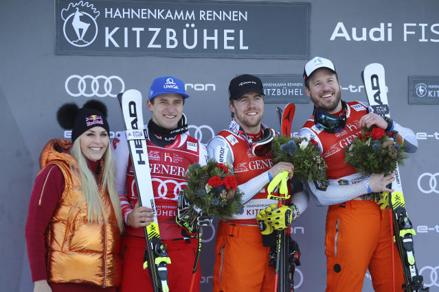 Norway's Kjetil Jansrud, right, winner of the alpine ski, men's World Cup super G, celebrates on the podium with former ski star United States' Lindsey Vonn, left, second placed Norway's Aleksander Aamodt Kilde, second from right, and third placed Austria's Matthias Mayer, in Kitzbuehel, Austria, Friday, Jan. 24, 2020. (AP Photo/Marco Trovati)
