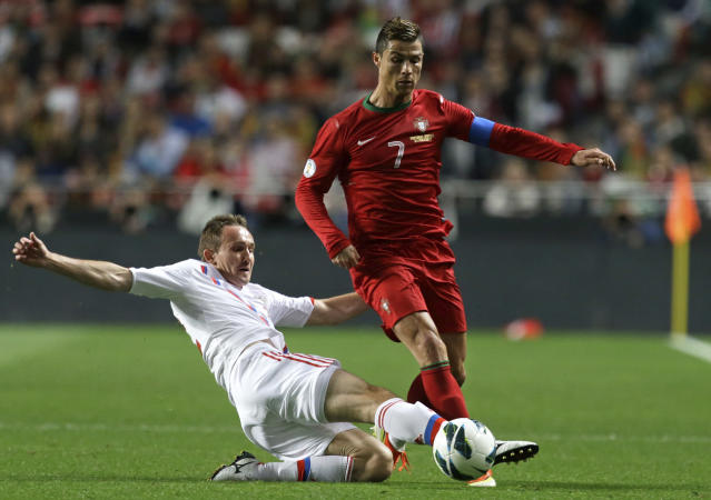 Russia's Alexei Kozlov, left, fails to stop Portugal's Cristiano Ronaldo during their 2014 World Cup qualifying group F soccer match Friday, June 7 2013, at the Luz stadium in Lisbon. (AP Photo/Armando Franca)
