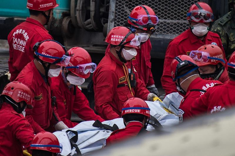 Rescue workers use a stretcher to carry the body of a male student, who was thought to be alive but died before being rescued from the remains of the Wei-Kuan complex which collapsed in the 6.4 magnitude earthquake, in Tainan on February 10, 2016 (AFP Photo/Anthony Wallace)