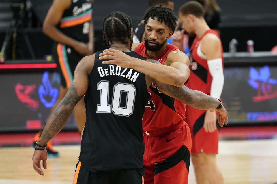 Toronto Raptors center Khem Birch congratulates San Antonio Spurs forward DeMar DeRozan (10) after an NBA basketball game Wednesday, April 14, 2021, in Tampa, Fla. (AP Photo/Chris O'Meara)