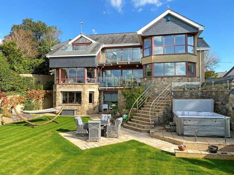 """<p>Dreaming of a coastal escape? This £2,500,000 detached home in Cornwall provides panoramic views over Restronguet Creek, perfect for watching the sun rise in the morning with a hot cup of coffee or set in the evening over dinner.</p><p> The home has two balconies and a series of garden-facing windows so you can look out over the stunning Cornish sea. The stunning property includes a detached double garage, plus a workshop, gym, and hot tub.</p><p><a href=""""https://www.rightmove.co.uk/estate-agents/agent/Lillicrap-Chilcott/Truro-32489.html"""" rel=""""nofollow noopener"""" target=""""_blank"""" data-ylk=""""slk:Currently on the market for £2,500,000 via Lillicrap Chilcott on Rightmove."""" class=""""link rapid-noclick-resp""""><u>Currently on the market for £2,500,000 via Lillicrap Chilcott on Rightmove.</u></a></p>"""