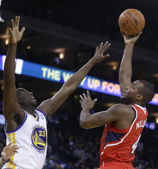 Atlanta Hawks' Paul Millsap, right, shoots over Golden State Warriors' Draymond Green (23 during the first half of an NBA basketball game Friday, March 7, 2014, in Oakland, Calif. (AP Photo/Ben Margot)