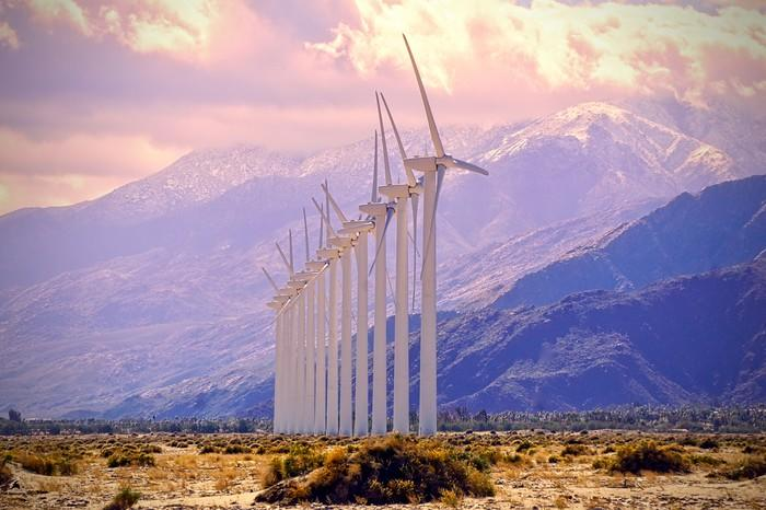 A row of wind turbines with the mountains in the background.