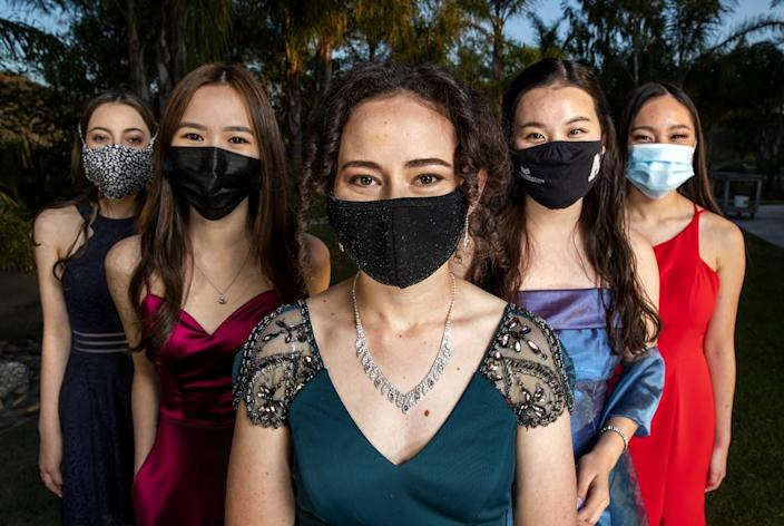 Five students in formal clothes and masks.