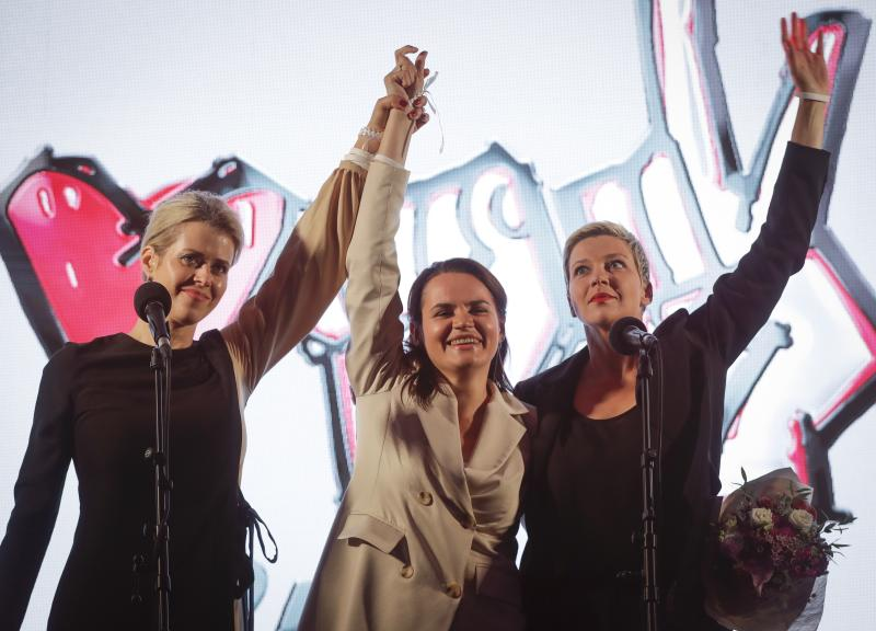 Maria Kolesnikova, a representative of Viktor Babariko, right, Svetlana Tikhanovskaya, candidate for the presidential elections, centre, and wife of non-registered candidate Valery Tsepkalo, Veronika Tsepkalo, left, gesture during meeting in support of Svetlana Tikhanovskaya in Minsk, Belarus, Thursday, July 30, 2020. Thousands of Tikhanovskaya's supporters gathered Thursday at her campaign rally in Minsk. The presidential election in Belarus is scheduled for August 9, 2020. (AP Photo/Sergei Grits)