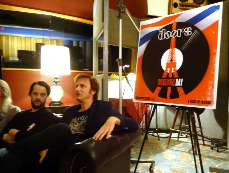 Michael Kurtz (R), co-founder of Record Store Day, and Lee Foster (L), manager of Electric Lady Studios, sit next to a poster advertising a special release by The Doors during a news conference on March 8, 2016