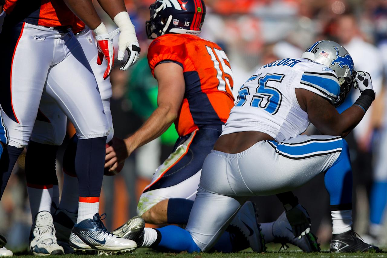 """DENVER, CO - OCTOBER 30:  Linebacker Stephen Tulloch #55 of the Detroit Lions reacts by """"Tebowing"""" after making a sack on quarterback Tim Tebow #15 of the Denver Broncos during the first quarter at Sports Authority Field at Mile High on October 30, 2011 in Denver, Colorado. (Photo by Justin Edmonds/Getty Images)"""