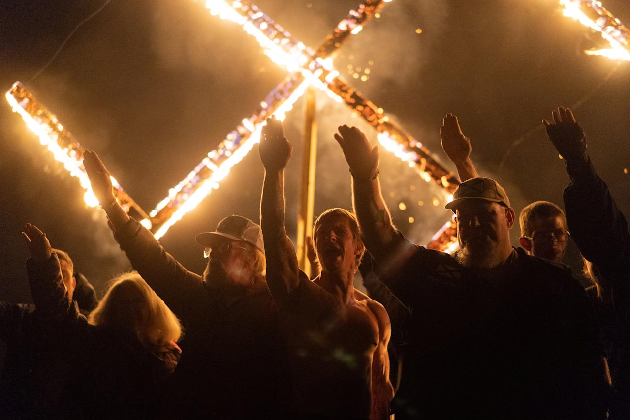 Supporters of the National Socialist Movement, a white nationalist political group, give Nazi salutes while taking part in a swastika burning at an undisclosed location in Georgia, U.S. on April 21, 2018. Picture taken on April 21, 2018. REUTERS/Go Nakamura     TPX IMAGES OF THE DAY