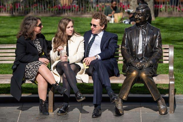 People sit and chat on a bench next to the Mr Bean statue in Leicester Square, London