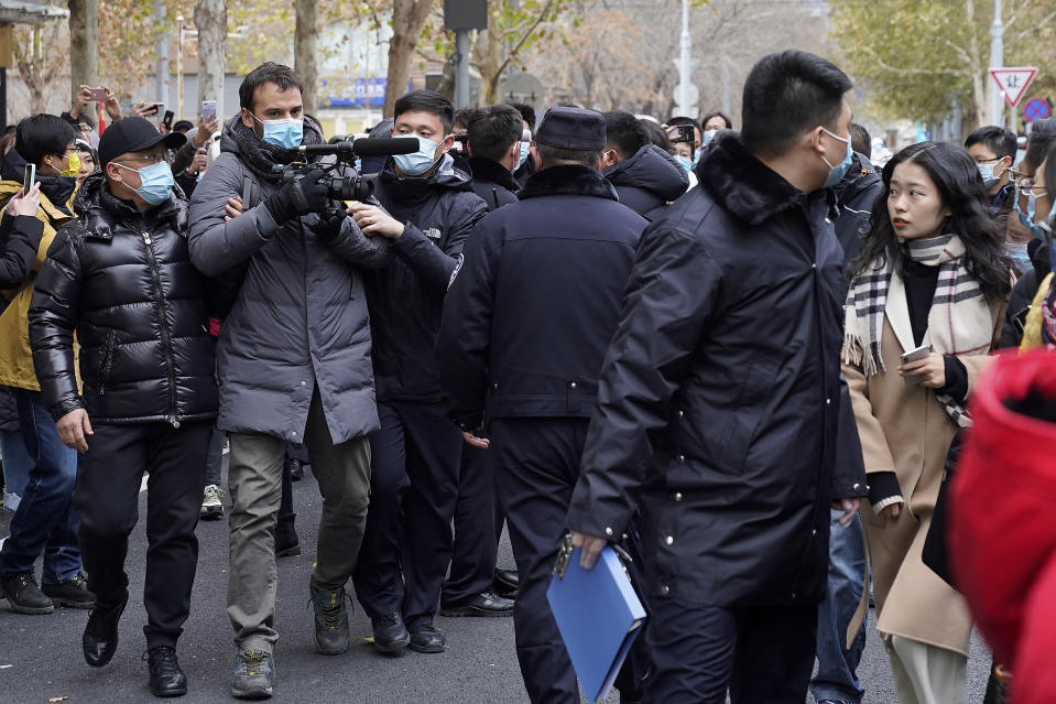 "Zhou Xiaoxuan, right, looks as Chinese policemen block a foreign journalist on her arrival at a courthouse in Beijing, Wednesday, Dec. 2, 2020. Zhou, a Chinese woman who filed a sexual harassment lawsuit against a TV host, told cheering supporters at a courthouse Wednesday she hopes her case encourages other ""victims of gender violence"" in a system that gives them few options to pursue complaints.(AP Photo/Andy Wong)"