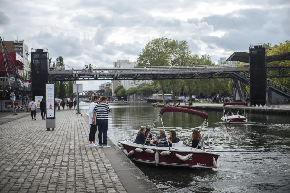 People enjoy a ride with a small boat on La Villette Canal, in Paris, France, Saturday, June 5, 2021. (AP Photo/Lewis Joly)