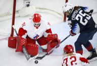 Russia goalie Anna Prugova, left, blocks a shot from Alex Carpenter, of the United States, during second period IIHF Women's World Championship hockey action in Calgary, Alberta, Tuesday, Aug. 24, 2021. (Jeff McIntosh/The Canadian Press via AP)