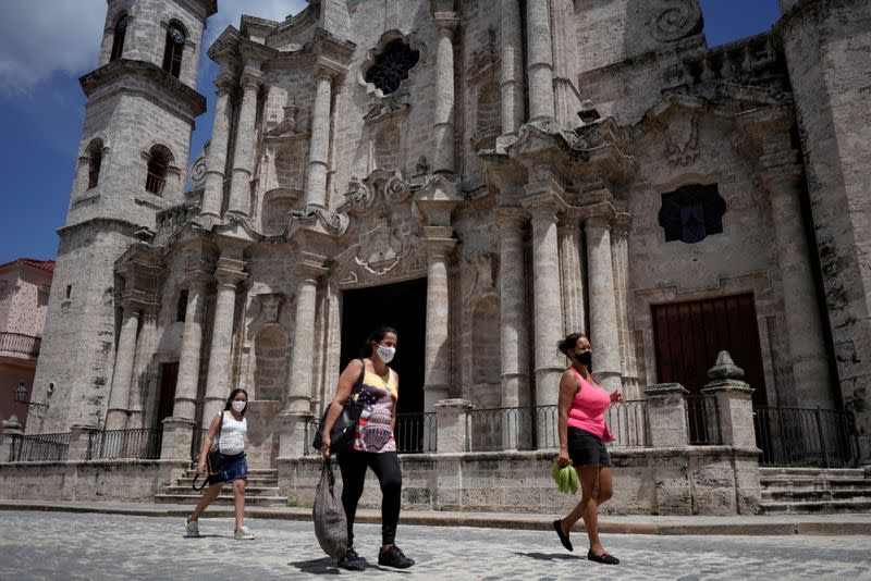 People pass by in front of the Havana's Cathedral