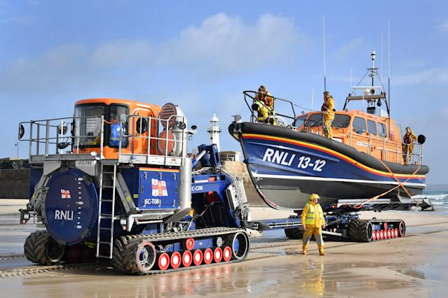 An RNLI boat is brought ashore at St Ives, Cornwall (PA)