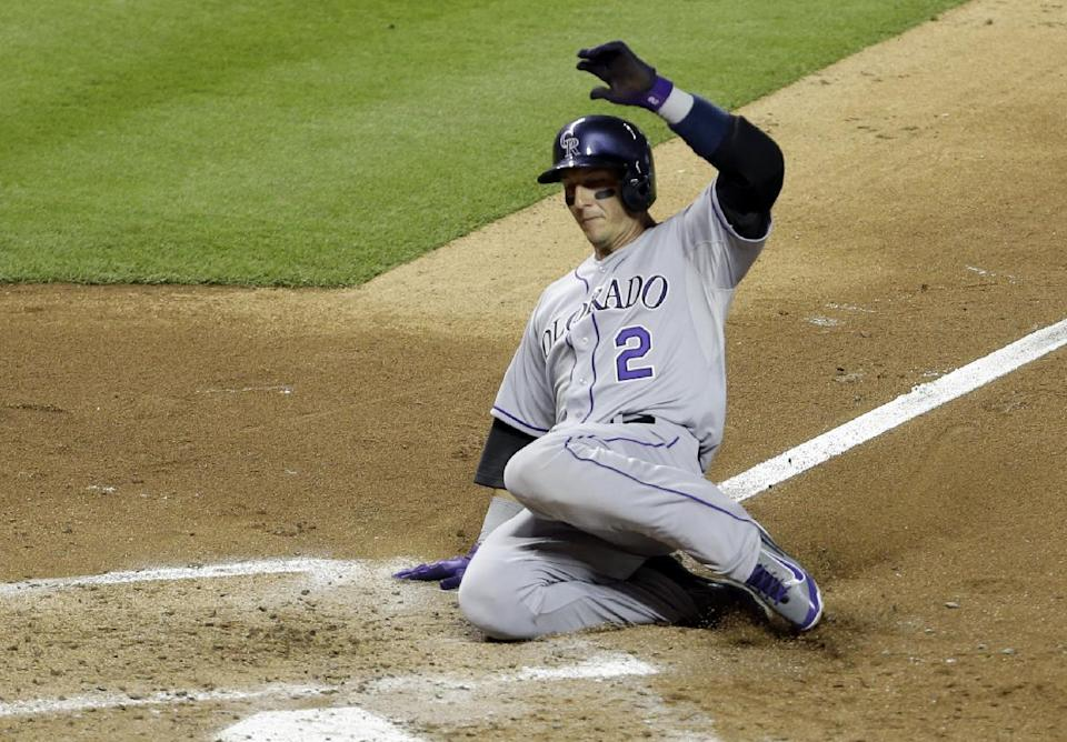 Colorado Rockies' Troy Tulowitzki (2) scores on a sacrifice fly by Wilin Rosario in the fourth inning of an MLB National League baseball game against the Miami Marlins, Tuesday, April 1, 2014, in Miami. (AP Photo/Lynne Sladky)