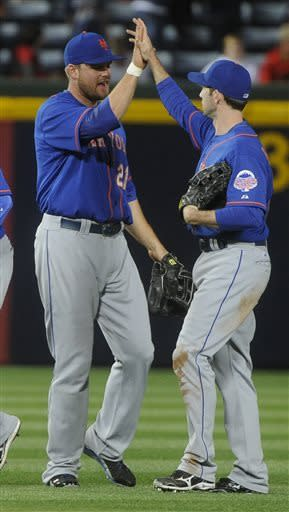 New York Mets left fielder Lucas Duda (21), and right fielder Mike Baxter (23) celebrate after playing the Atlanta Braves during a baseball game, Friday, May 3, 2013, in Atlanta. New York won 7-5. (AP Photo/John Amis)