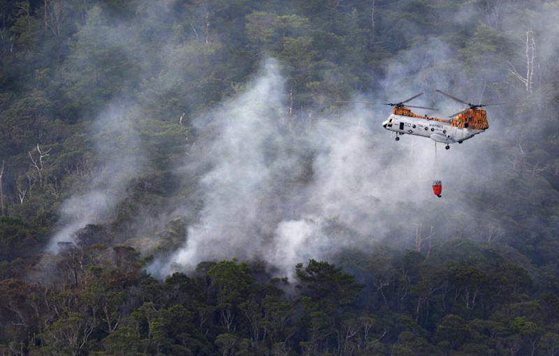 ADD TYPE OF HELICOPTER THAT FLIES OVER CRASH SITE AND WHAT IT DOES - Smoke billows from the crash site of U.S. air force rescue helicopter HH-60 at Camp Hansen as U.S. marine helicopter CH46 flies over to drop water, on the southern island of Okinawa, Japan, Monday, Aug. 5, 2013. The HH-60 rescue helicopter crashed in a training area at Camp Hansen with four crew members on board, the U.S. Air Force said in a statement. The status of the crew members is unknown, it said. (AP Photo/Kyodo News) JAPAN OUT, MANDATORY CREDIT