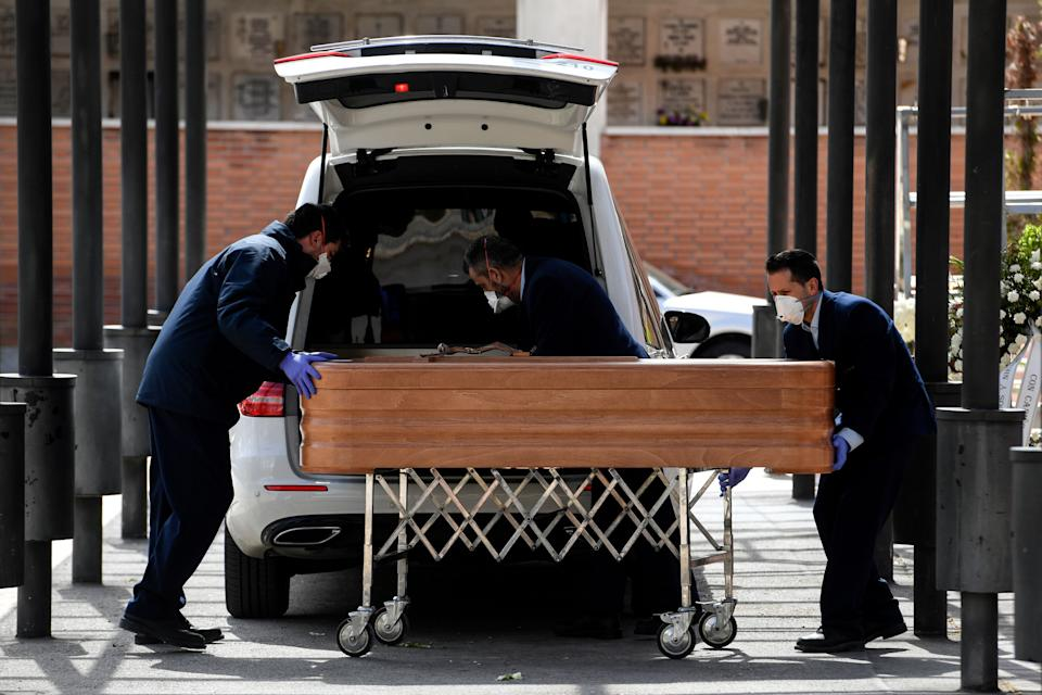 TOPSHOT - Mortuary employees wearing face masks wheel a coffin into the crematorium of La Almudena cemetery in Madrid on March 24, 2020 during the funeral of a COVID-19 coronavirus victim. - Spain has been one of the worst-hit countries, logging the third-highest number of deaths with the latest figures showing a toll of 2,696. (Photo by OSCAR DEL POZO / AFP) (Photo by OSCAR DEL POZO/AFP via Getty Images)