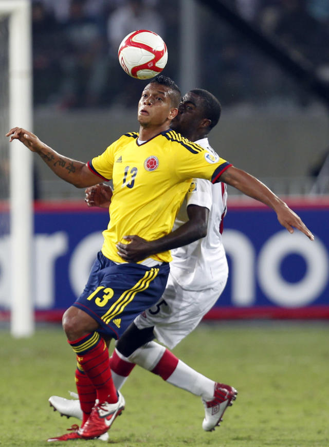 """In This June 3, 2012, file photo, Colombia's Fredy Guarin, left, and Peru's Christian Ramos battle for the ball during a 2014 World Cup qualifying soccer game in Lima, Peru. The """"Coffee Growers"""" ripped through qualification, hammering Uruguay 4-0 on their way to earning 30 points from 16 matches. Falcao sealed qualification with two late goals against Chile, coming from behind for a 3-3 home draw. (AP Photo/Martin Mejia,File)"""