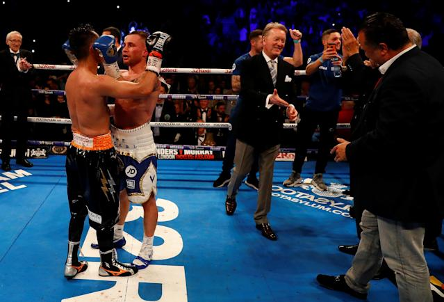 Boxing - Carl Frampton v Nonito Donaire - WBO Interim Featherweight World Title - SSE Arena, Belfast, Britain - April 21, 2018 Carl Frampton hugs Nonito Donaire after winning the fight as promoter Frank Warren looks on Action Images via Reuters/Jason Cairnduff
