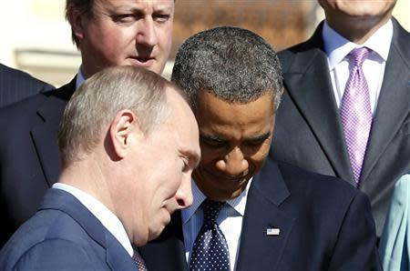 Russian President Vladimir Putin (L) walks past U.S. President Barack Obama (C) during a group photo at the G20 Summit in St. Petersburg in this September 6, 2013 file picture. REUTERS/Kevin Lamarque