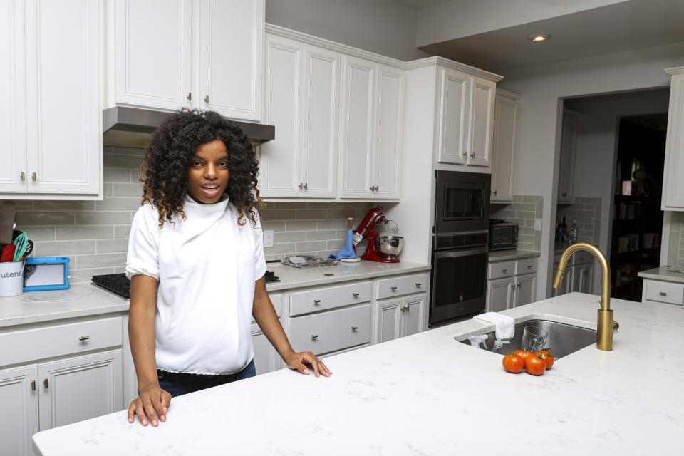 Crystal Marie McDaniels poses in front of her home in Charlotte, N.C., on Friday, July 9, 2021. Mcdaniels said buying a house was crucial for her because she wants to pass on wealth to her son someday, giving him an advantage she never had. So when the loan officer told her the deal wasn't going to happen, she refused to give up. (AP Photo/Nell Redmond)