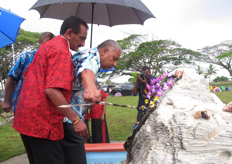 In this Nov. 7, 2013 photo, Fiji's Prime Minister Voreqe Bainimarama, center, pulls a ribbon to open a picnic park in Suva, Fiji. Seven years after seizing power in a military coup, Bainimarama, the 59-year-old former naval officer, who also goes by the name Frank, has promised to hold democratic elections in this South Pacific island nation of 900,000. More than half a million Fijians have registered to vote, hoping to end a quarter-century of turmoil. The international community, which imposed sanctions after the coup, has offered a cautious welcome. (AP Photo/Nick Perry)