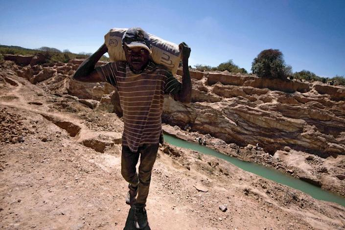 A man carries a bag at a mine for copper and cobalt in another part of DR Congo (AFP Photo/JUNIOR KANNAH)