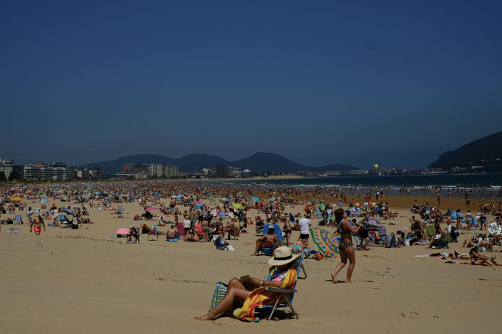FILE - In this file photo dated Saturday, July 17, 2021, people on the beach during a summer's day, in Laredo, northern Spain. Europe's famed summer holiday season is in full swing, but efforts to inoculate people against coronavirus are not taking a break. From France's Mediterranean coast to Italy's Adriatic beaches, health authorities are trying to make a COVID-19 shot as much a part of this summer as sunscreen and shades. (AP Photo/Alvaro Barrientos, FILE)