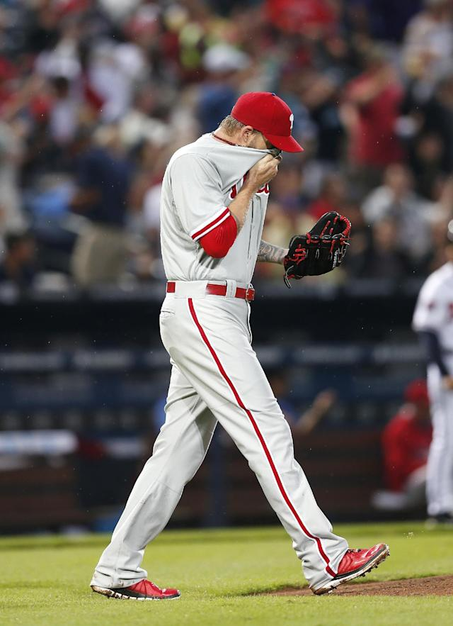 Philadelphia Phillies starting pitcher A.J. Burnett wipes his face as he walks back to the mound after giving up a two-run single to Atlanta Braves' Andrelton Simmons in the second inning of a baseball game in Atlanta, Friday, July 18, 2014. (AP Photo/John Bazemore)