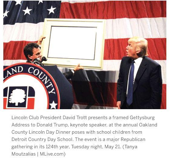 This is a screenshot of photo taken by MLive.com of the GOP Michigan dinner where Trump was given a framed copy of the Gettysburg Address, not a man of the year award. (Photo: MLive.com)