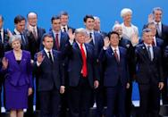 U.S. President Donald Trump, Britain's Prime Minister Theresa May, French President Emmanuel Macron and Japanese Prime Minister Shinzo Abe wave hands during a family photo at the G20 leaders summit in Buenos Aires, Argentina November 30, 2018. REUTERS/Kevin Lamarque