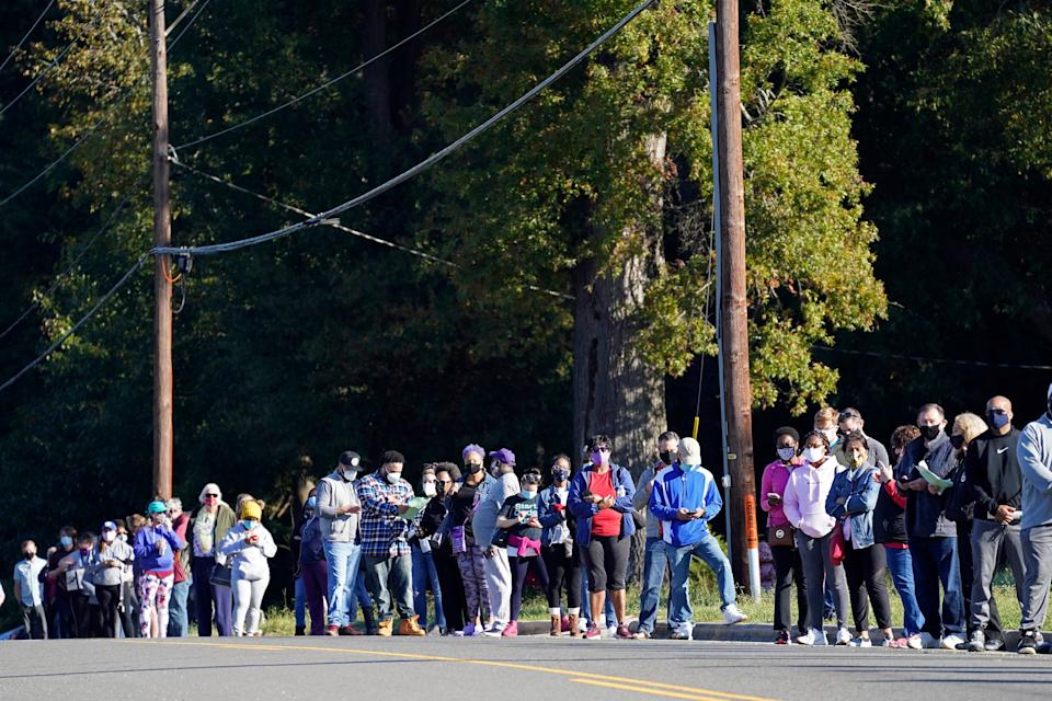 Early voters form a line along South Alston Ave. to cast their ballots at the South Regional Library polling location in Durham, N.C., Thursday, Oct. 15, 2020.