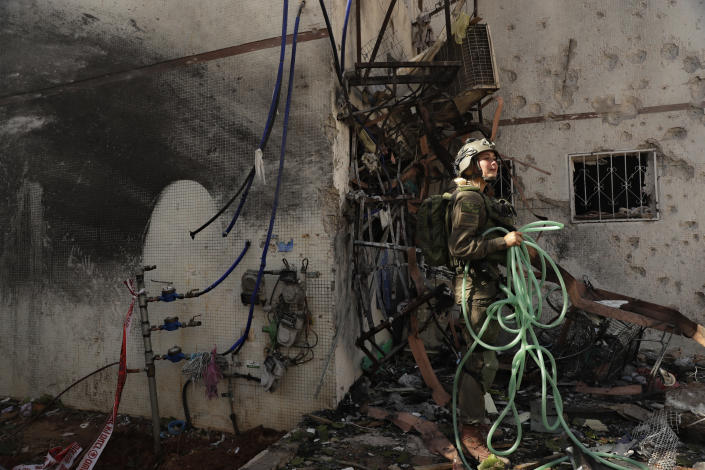 An Israeli soldier inspects damage to an apartment in a residential building after it was hit by a rocket fired from the Gaza Strip, in Ashdod, southern Israel, Monday, May 17, 2021. (AP Photo/Maya Alleruzzo)