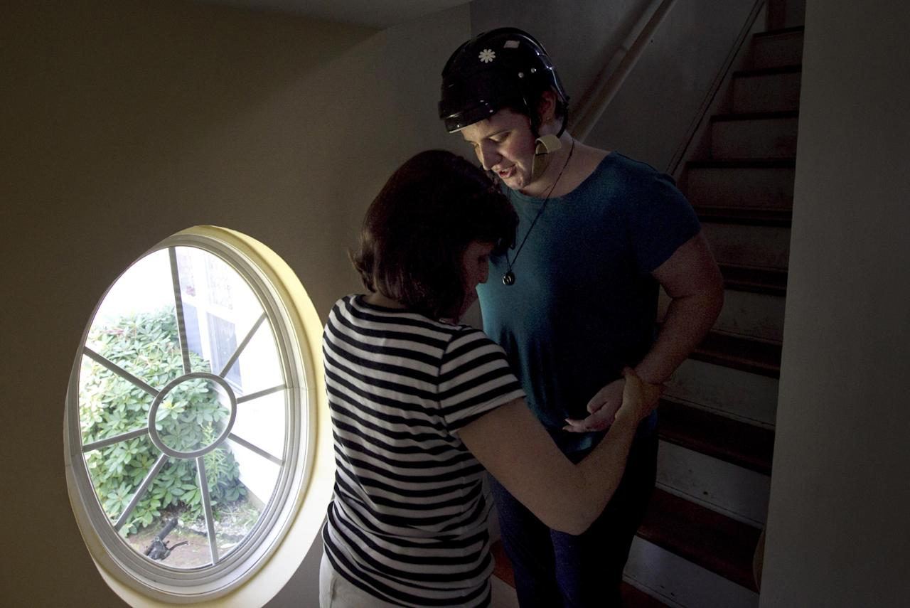 In this Thursday, Aug. 2, 2012 photo, Meg Theriault is assisted by her mother, Deb Theriault, left, as they descend a flight of stairs at their home in Salisbury, Mass. It was the first time Meg was home since being involved in a multi-fatal single-car accident two-and-a-half months earlier. (AP Photo/Steven Senne)