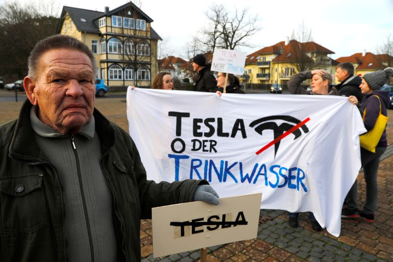 FILE PHOTO: Demonstrators hold anti-Tesla posters during a protest against plans by U.S. electric vehicle pioneer Tesla to build its first European factory and design center near Berli