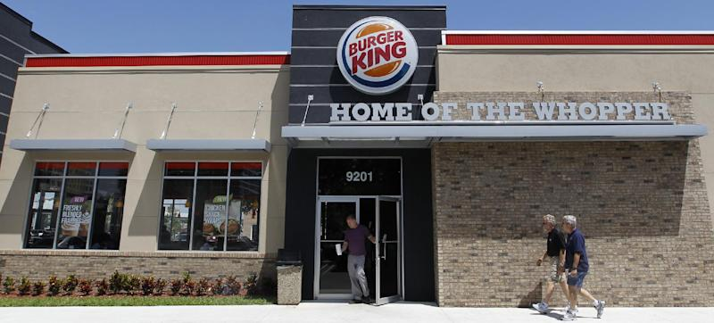 In this March 28, 2012 photo, a patron leaves a Burger King restaurant in Miami. On Monday, April 2, 2012, Burger King launches 10 menu items including smoothies, frappes, specialty salads and snack wraps in a star-studded TV ad campaign. It's the biggest menu expansion since the chain opened its doors in 1954. (AP Photo/Luis M. Alvarez)